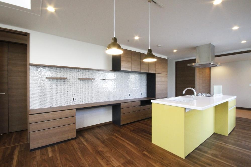 収納とデスクが1つになったワークカウンター - イエローのアイランドキッチンをアクセントに、住まいに合わせて造作したワークカウンター。収納や飾り棚、壁面をモザイクタイルで装飾し、デザインと機能が両立した仕上がりに。 -  -