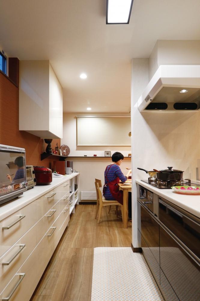 キッチン越しにダイニングを見る - キッチンの後ろのロングカウンターは、ダイニングまでのびる5.5mの長さ。既製品の収納にカウンターを造作して1つのインテリアにみせています。 -  -