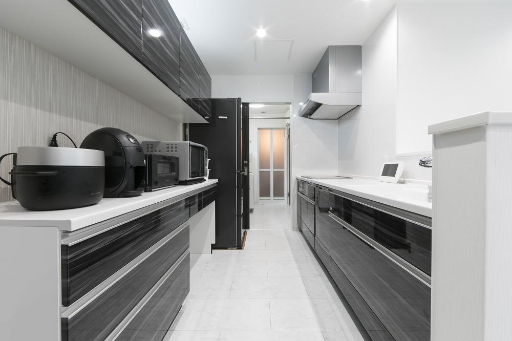 キッチン - 奥のユーティリティーまでスムーズに移動できるキッチンは、家事の同時進行も快適 -  -