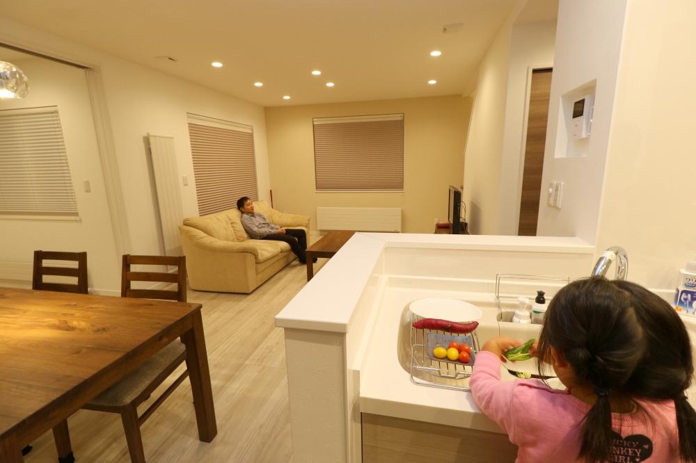 キッチンからみたリビング - リビングに対してセミオープンにしたキッチン。コンロ側を壁で隠すことで、空間の印象がスッキリします。 -  -