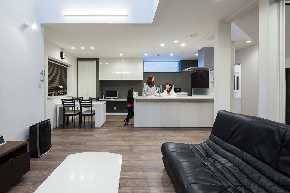 リビング・ダイニング・キッチン - キッチンやドア、家具をモノトーンで演出しながら、床には木目の温もりを。ダイナミックな吹抜けの空間で過ごす時間が「寛げますね」とご主人。 -  -