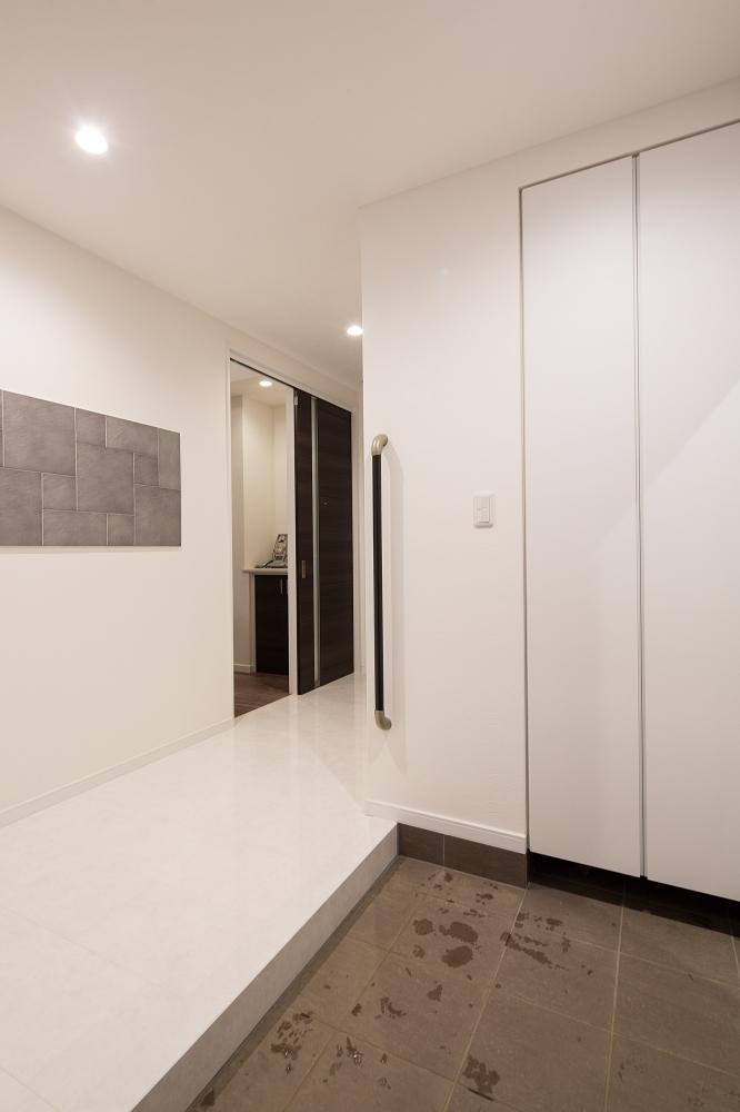 玄関ホール - 土間タイルと壁面のエコカラットのデザインを合わせ、白い建具や床が高級感を醸す玄関ホール。床暖房になっており、冬も暖かさが家族を迎えてくれます。 -  -