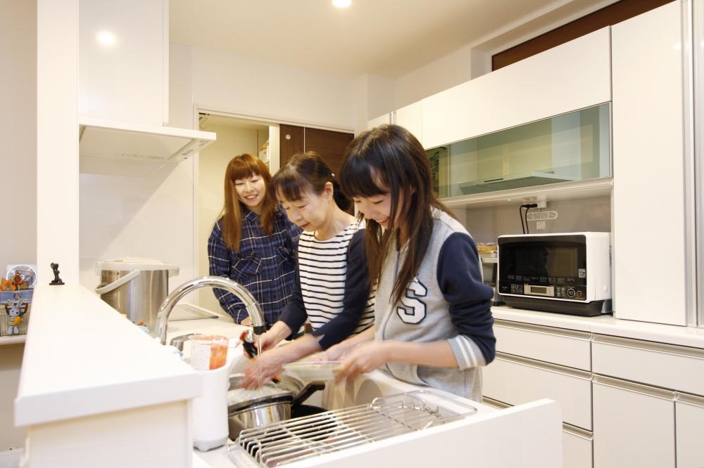 三世代の女性が集う1階のキッチン - 3人が並んで立てる広さが快適です。リビングやダイニングにいる人と会話をしながら、楽しく調理できるようになりました。 -  -