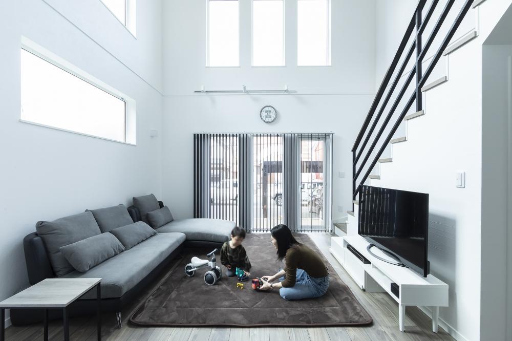吹抜けのリビング - 3連のトップライトやワイドなガラス窓。澄んだ光がどこまでも広がり、白い壁が優しくうけとめるリビング。 -  -