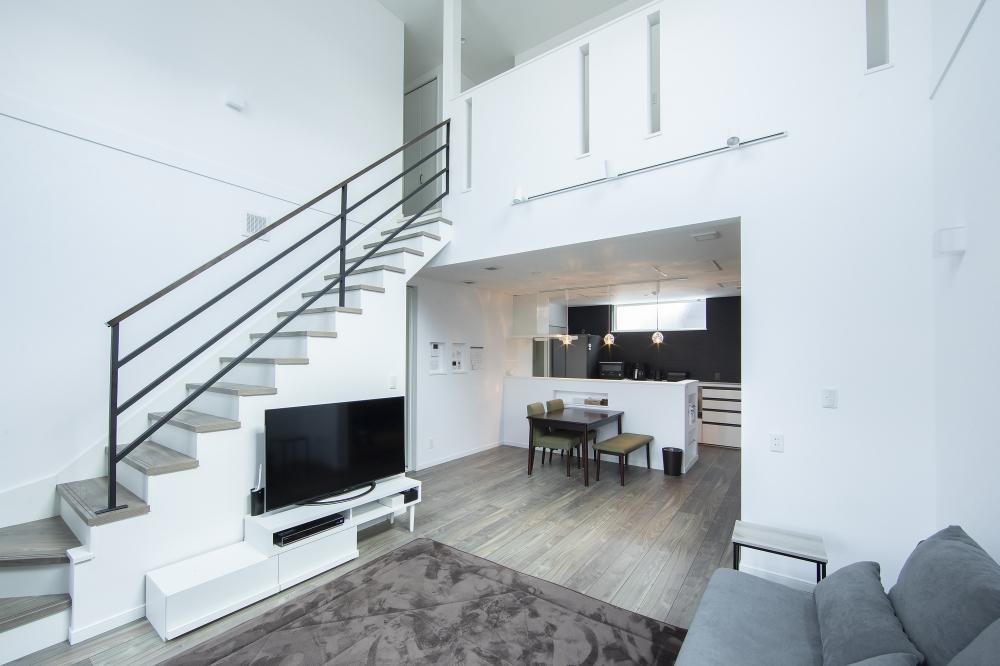 リビング・ダイニング・キッチン - 階段はフロアから2ステップをL字型にし、ゆるやかに2階までつなげています。開放的なリビングを眺めながら、DKは落ち着いて食事ができる空間。 -  -