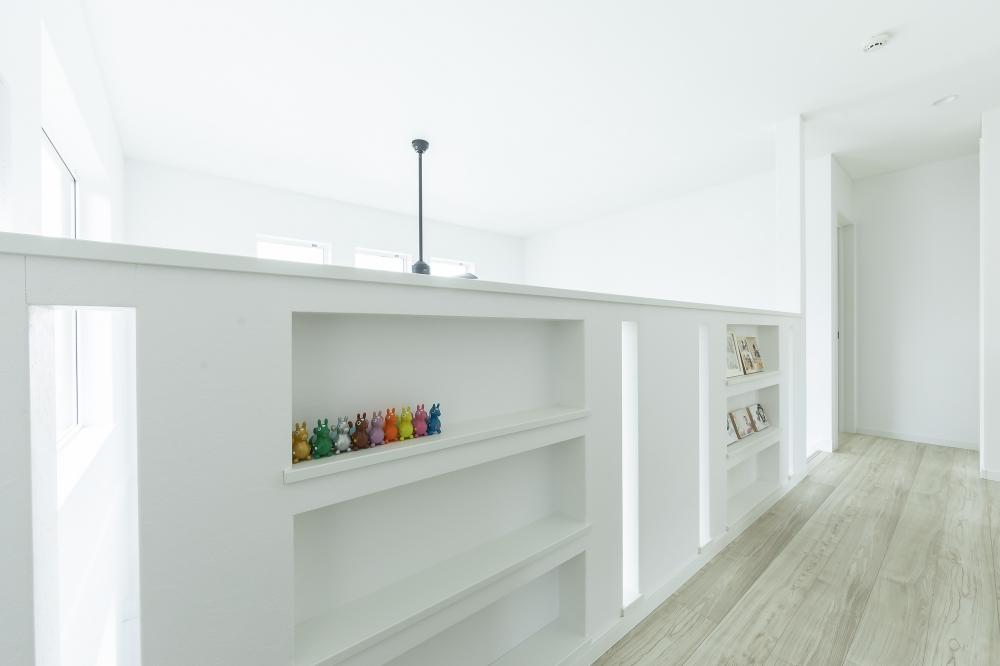 - 吹抜けとつながるホールは、写真や本、雑貨が飾れるライブラリースペースに。物干しポールを設置し、ドライエリアも兼ねています。 -  -