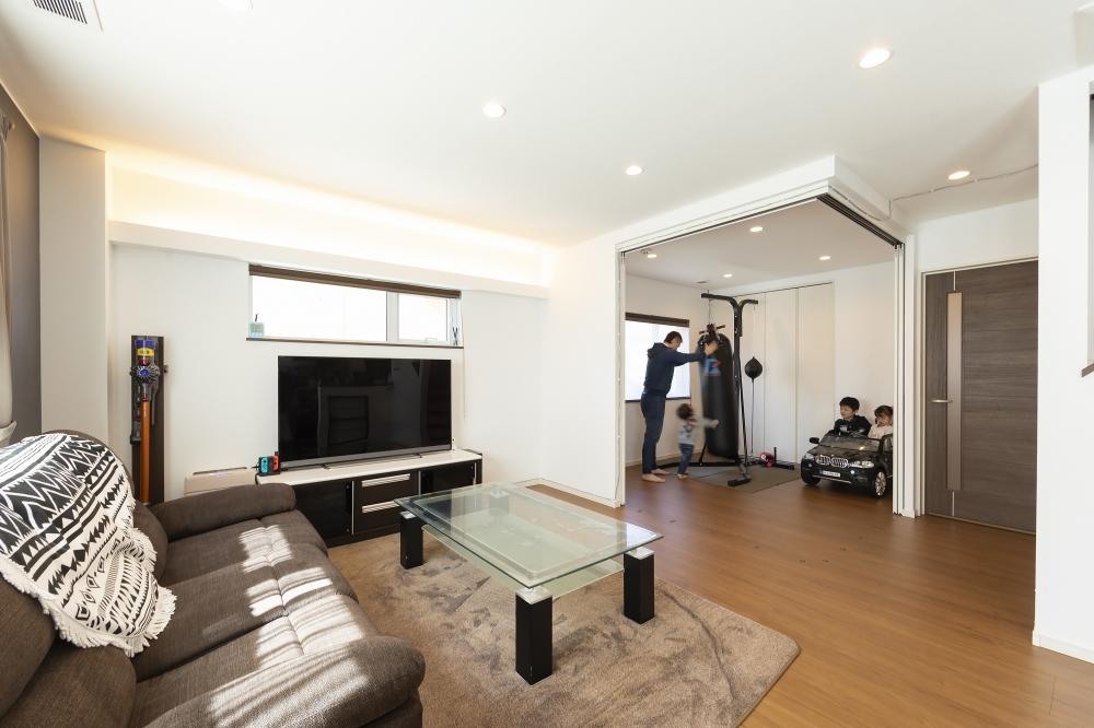 リビングと、トレーニングルームを兼ねた洋室 - 陽射しがすみずみまで届く、暖かなリビング。サンドバッグが置かれた洋室は、収納もあり個室にできます。 -  -
