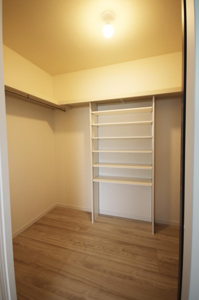寝室横のウォークインクローゼットです。3畳分あり、左右対称にステンパイプを設けておりますので、ご主人と奥様の衣服をそれぞれ掛けておくことが可能です。正面の棚にはバックや帽子などの小物類も収納できます -  -  -